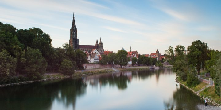 Long exposure of the river Danube and Ulm skyline with Ulmer Minster (cathedral) against blue sky